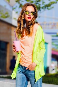 Junge stilvolle blonde hipsterfrau in der kühlen sonnenbrille mit cocktail, der im freien aufwirft