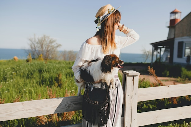 Junge stilvolle frau auf dem land, einen hund haltend