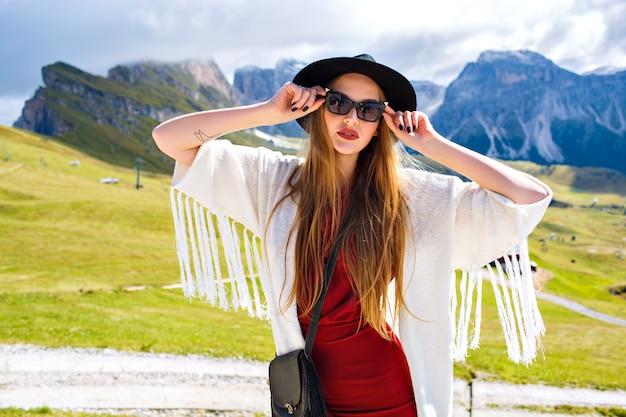 Junge stilvolle frau, die an den alpenbergen im boho-mode-outfit aufwirft