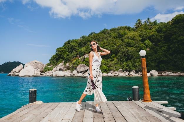 Junge stilvolle frau, die auf pier steht, zu fuß geht, musik auf kopfhörern, sommerkleidung, weißem rock, handtasche, azurblauem wasser, landschaftshintergrund, tropischer lagune, urlaub, reisen in asien hörend hört