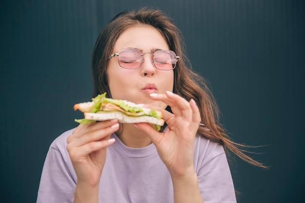 Junge stilvolle frau, die das leckere köstliche sandwich während des mittagessens genießt