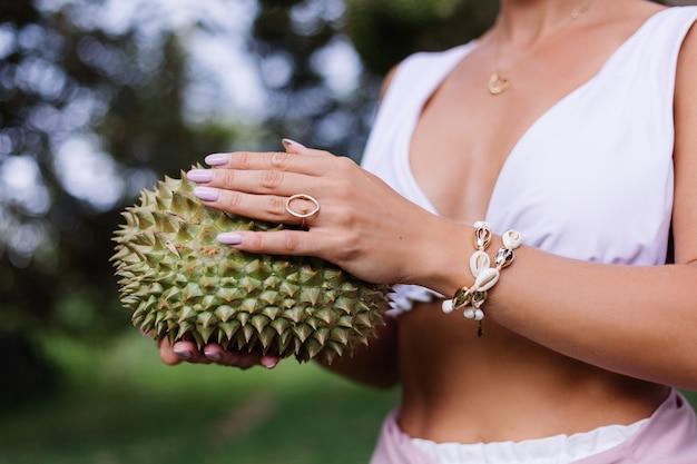 Junge stilvolle frau, die durianfrucht hält
