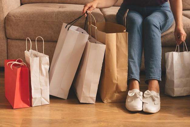 Junge stilvolle frau, die einkaufstaschen hält und auf einer couch sitzt
