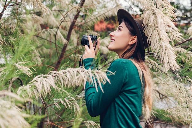 Junge stilvolle frau, die fotos unter verwendung der kompaktkamera im sommergarten macht. mädchen, das hobby im parkschießen blühender bäume genießt