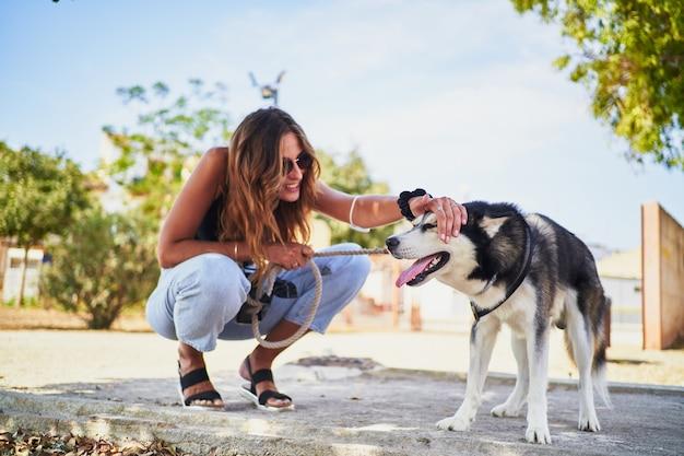 Junge stilvolle frau, die ihren sibirischen husky für im park streichelt
