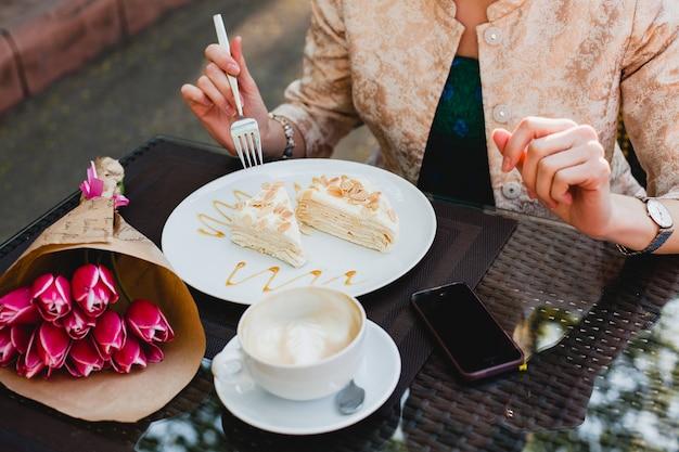 Junge stilvolle frau, die im café sitzt, tasse cappuccino hält und leckeren kuchen isst,