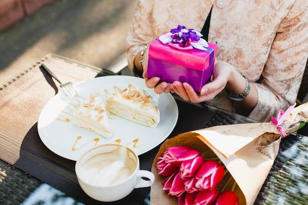 Junge stilvolle frau, die im café sitzt und geschenkbox hält
