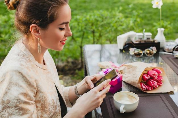 Junge stilvolle frau, die im café sitzt und smartphone hält