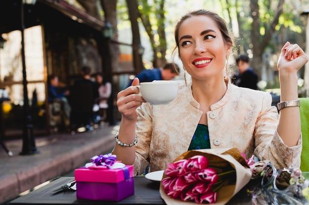 Junge stilvolle frau, die im café sitzt und tasse cappuccino hält