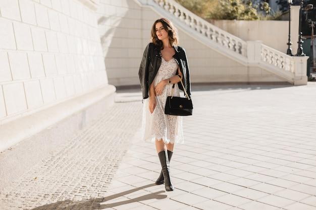 Junge stilvolle frau, die in der straße im modischen outfit geht, geldbörse hält, schwarze lederjacke und weißes spitzenkleid tragend, frühlingsherbstart, posierend, hohe lederstiefel