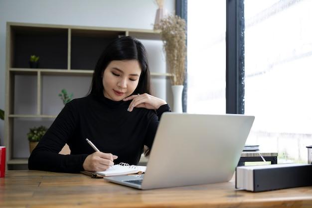 Junge stilvolle frau, die mit laptop-computer arbeitet.
