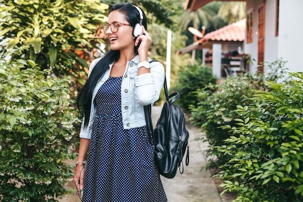 Junge stilvolle frau, die mit smartphone geht, musik auf kopfhörern, sommerferien hörend