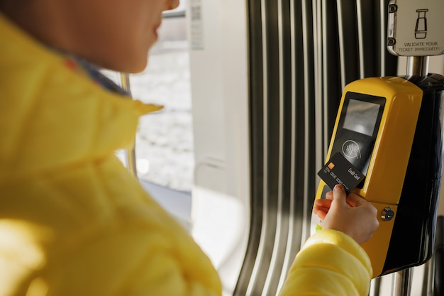 Junge stilvolle frau, die öffentlich elektronische transportmittel der kartenstanzmaschine verwendet. mädchen, das kontaktlos mit bankkarte für die öffentlichen transportmittel in der tram zahlt
