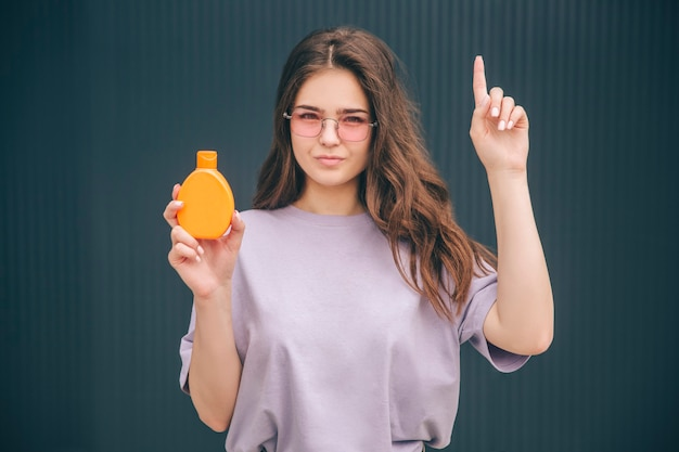 Junge stilvolle frau, die orange flasche mit sonnenschutz spf gesichtspflegeschutz hält