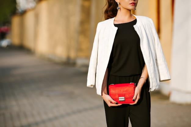 Junge stilvolle frau geht in die stadt mit einer roten trendigen tasche.