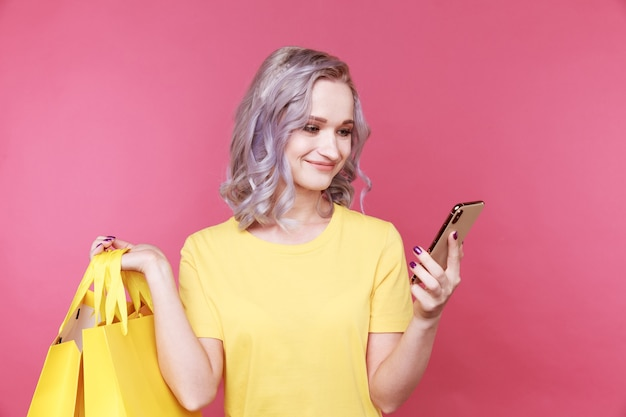 Junge stilvolle frau im gelben t-shirt, das telefon und das gleiche farbpaket lokalisiert hält