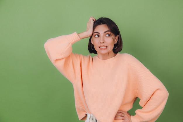 Junge stilvolle frau im lässigen pfirsichpullover und in den orangefarbenen gläsern lokalisiert auf grüner olivenwand beschäftigt hand auf kopfblick beiseite kopienraum