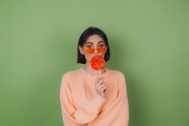 Junge stilvolle frau im lässigen pfirsichpullover und in den orangefarbenen gläsern lokalisiert auf grüner olivenwand mit orangefarbenem lutscher senden luftkusskopierraum