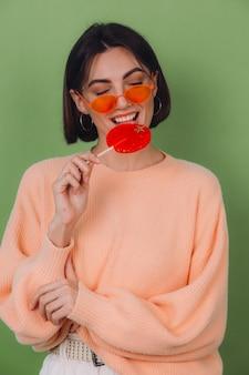 Junge stilvolle frau im lässigen pfirsichpullover und in den orangefarbenen gläsern lokalisiert auf grüner olivenwand mit positivem lächelnkopienraum des orange lutschers