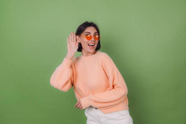 Junge stilvolle frau im lässigen pfirsichpullover und in den orangefarbenen gläsern lokalisiert auf grüner olivenwand neugierig versuchen zu hören, was sie mit der hand durch ohrkopierraum sagen