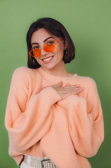 Junge stilvolle frau im lässigen pfirsichpullover und in den orangefarbenen gläsern lokalisiert auf positivem halten der hände der grünen olivenwand gefaltet auf brust, herzkopierraum