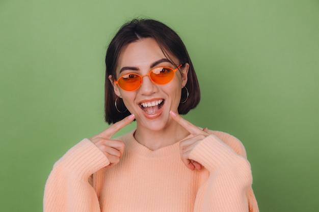 Junge stilvolle frau im lässigen pfirsichpullover und in den orangefarbenen gläsern lokalisiert auf positivem lächeln der grünen olivenwand, das auf weiße zähne mit zeigefingerkopierraum zeigt