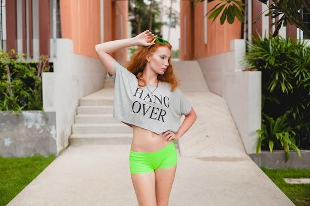 Junge stilvolle frau in der fitnessbekleidung, im ingwerhaar, in den grünen shorts, in der sonnenbrille, im übergroßen t-shirt, hängen vorbei, party-stimmung. spaß haben, sexy, heiß, flirtend, schlanker körper, sportlich,