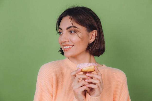 Junge stilvolle frau in lässigem pfirsichpullover lokalisiert auf grüner olivenwand mit glücklichem kopienraum des rosa donuts