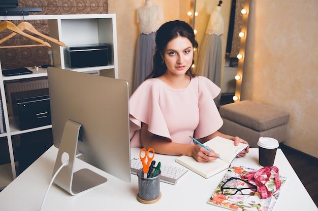Junge stilvolle frau in rosa luxuskleid, die im büro am computer arbeitet