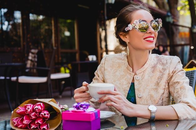 Junge stilvolle frau, mode-sonnenbrille, die im café sitzt und tasse cappuccino hält, lächelt
