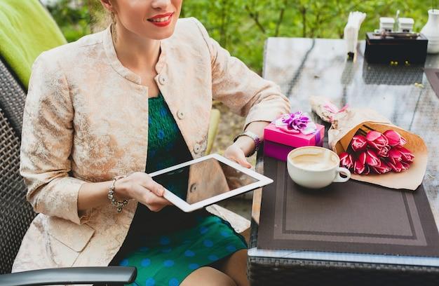 Junge stilvolle glückliche frau, die im café sitzt und tablette hält