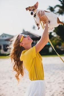 Junge stilvolle hipster-frau, die das gehen spielt, spielt hundwelpe jack russell, tropischer park, lächelnd und hat spaß, urlaub, sonnenbrille, mütze, gelbes hemd, strandsand
