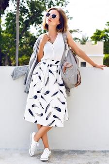 Junge stilvolle hipster-frau, die rucksack-sonnenbrille, vintage-midirock und turnschuhe trägt und auf der straße an einem schönen sonnigen sommertag, helle frische farben geht.