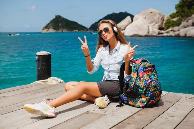 Junge stilvolle hipster-frau, die um die welt reist, sitzt auf dem pier, fliegersonnenbrille, kopfhörer, hört musik, urlaub, rucksack, jeanshemd, fröhliche, tropische insellagune