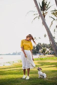 Junge stilvolle hipsterfrau, die das gehen und spielen mit hund im tropischen park hält, lächelt und spaß hat, urlaub, sonnenbrille, mütze, gelbes hemd, strandsand