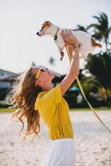 Junge stilvolle hipsterfrau, die das gehen und spielen mit hund im tropischen park hält, lächelt und spaß hat