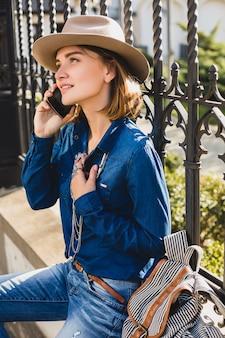 Junge stilvolle hübsche frau, die lächelt und auf ihrem telefon spricht, gekleidet in jeanshemd und jeans
