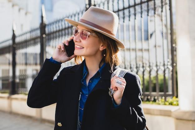 Junge stilvolle hübsche frau lächelnd, glücklich, überrascht, auf ihrem telefon sprechend, gekleidet in dunkelblauem mantel und jeanshemd