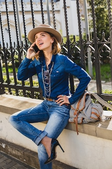 Junge stilvolle hübsche glückliche frau, die lächelt und auf ihrem telefon spricht, erstaunt