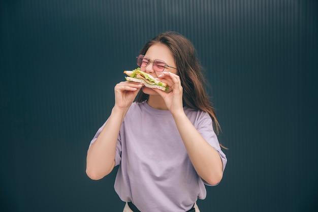 Junge stilvolle hungrige frau beißt ein stück frisches sandwich