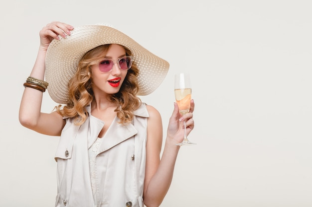 Junge stilvolle lächelnde blonde frau im großen hut und in der sonnenbrille, die glas champagner auf einer glücklichen partei halten
