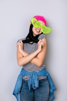 Junge stilvolle lächelnde frau, die rosa hut und große lustige brille trägt, die mit ihren haaren spielen