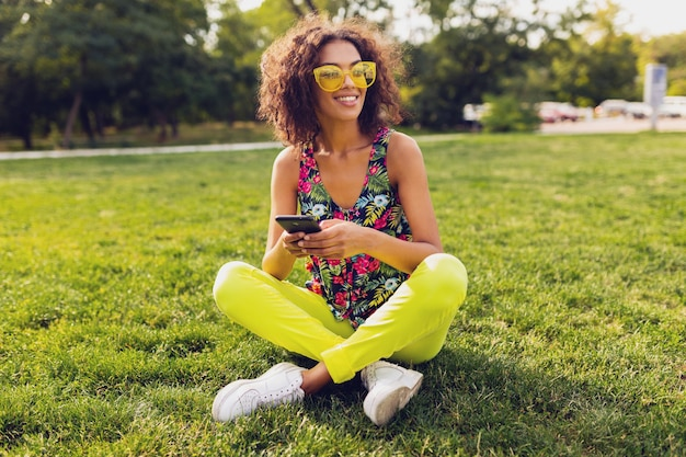 Junge stilvolle lächelnde schwarze frau, die smartphone verwendet, das musik auf kabellosen kopfhörern hört, die spaß im park haben, bunte art der sommermode, auf gras sitzend, gelbe sonnenbrille