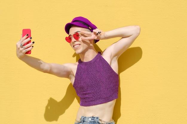 Junge stilvolle nicht-binäre person, die selfies mit einem mobiltelefon macht, während sie im freien gegen eine gelbe wand steht. nicht-binäres gender-konzept.