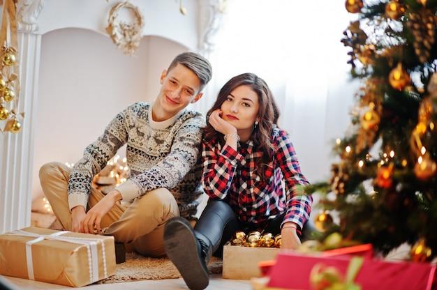 Junge stilvolle paare mit weihnachtsgeschenken und dekoration des neuen jahres