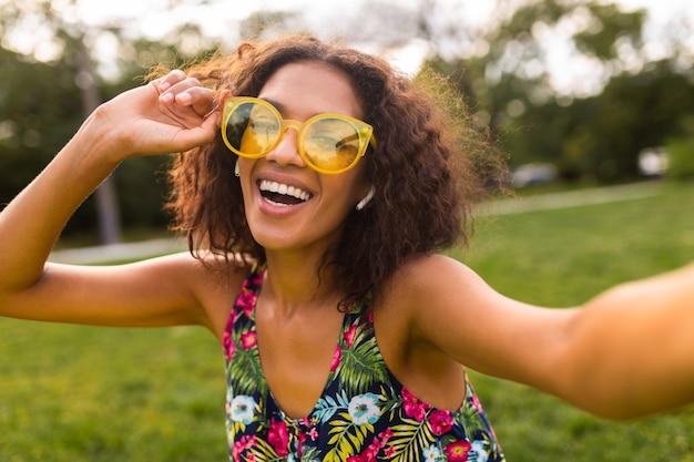 Junge stilvolle positive schwarze frau, die selfie-foto macht, das musik auf drahtlosen kopfhörern hört, die spaß im park, sommermode-art, buntes hipster-outfit haben