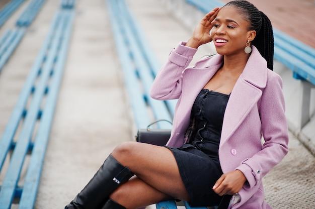 Junge stilvolle schöne afroamerikanerfrau in der straße an den stadion tribünen, die mode outfit mantel tragen.