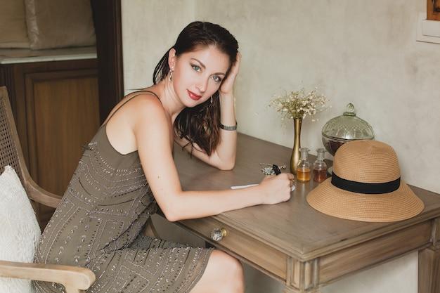 Junge stilvolle schöne frau, die am tisch im hotelzimmer des resorts sitzt und einen brief schreibt, denkend, raffiniert, lächelnd, glücklich, böhmisches outfit, stift, strohhut, vintage-stil haltend