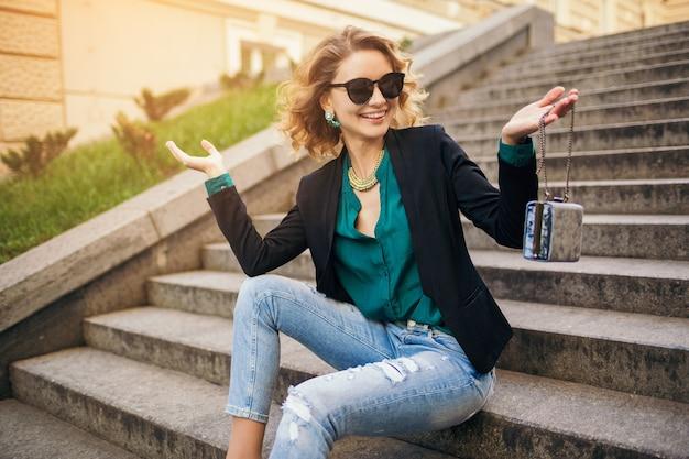 Junge stilvolle schöne frau, die auf treppe in der stadtstraße sitzt und jeans, schwarze jacke, grüne bluse, sonnenbrille, geldbeutel, eleganten stil, sommermodetrend, lächelnd trägt