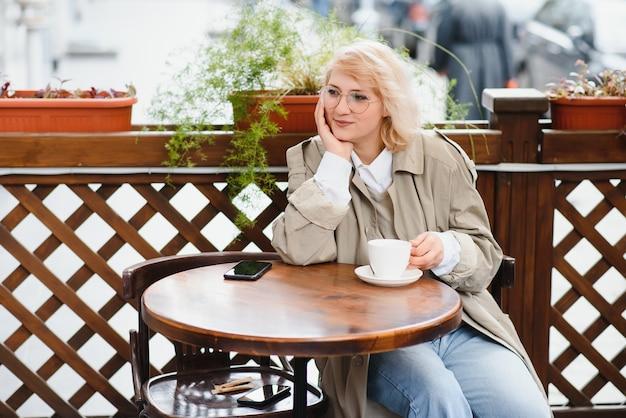 Junge stilvolle schöne frau, die im stadtcafé in der straße sitzt